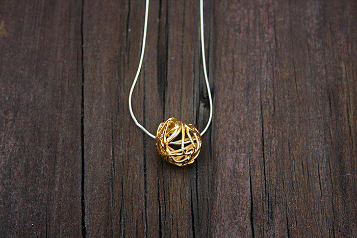 Goldplated silver 'mesh' pendant by a ring to it