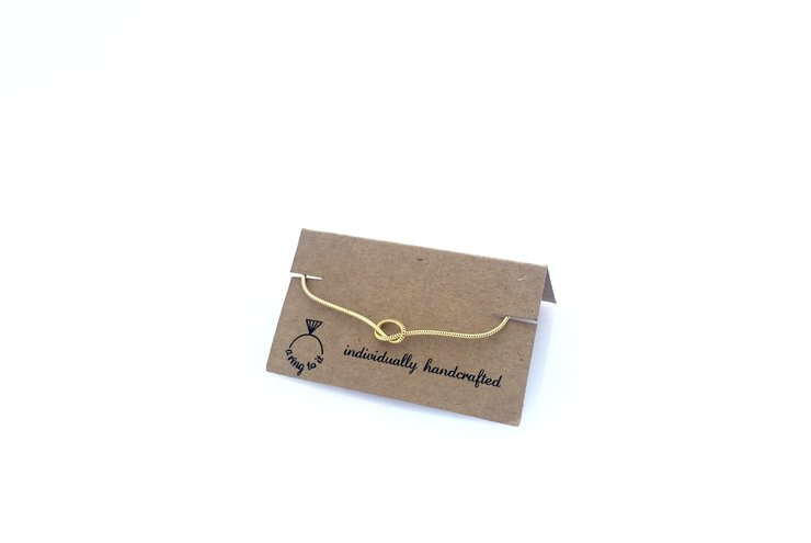 'tie the knot' gold plated silver bracelet  by a ring to it
