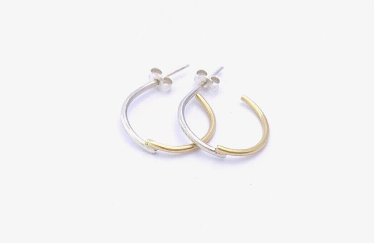Silver and brass 'criss cross' earrings by a ring to it