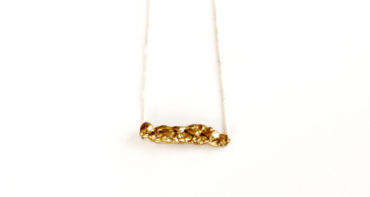 Brass 'bubblegum' bar pendant on silver chain by a ring to it